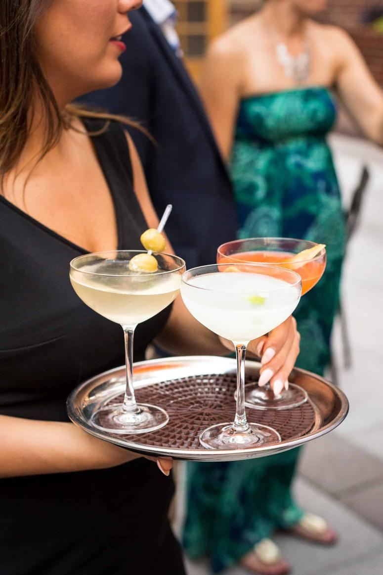 Photo of a server with champagne coupes and cocktails on a silver tray.