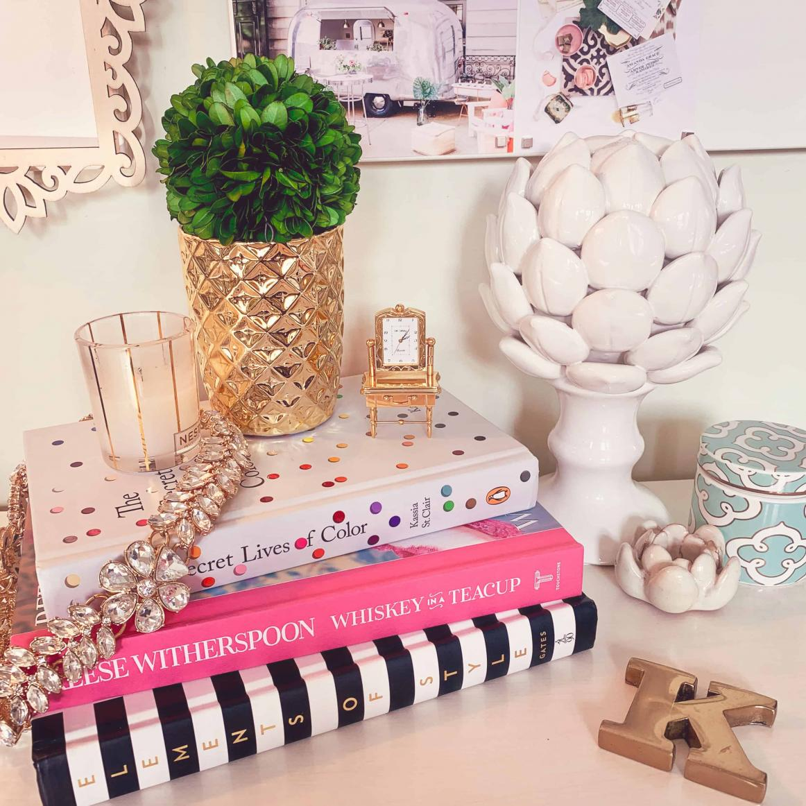 Styled desk featuring design books, candle and ceramic artichoke finial.