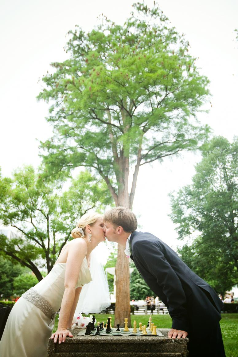 Photo of a bride and groom kissing over a chess board in Dupont Circle, Washington DC