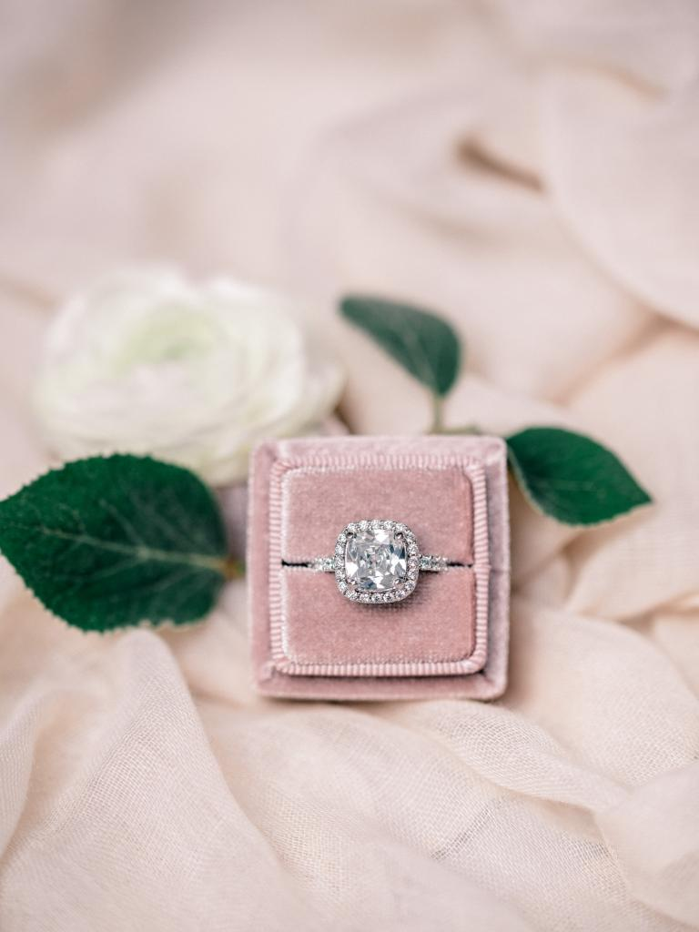 Photo of a ring in a pink ring box with a white flower.