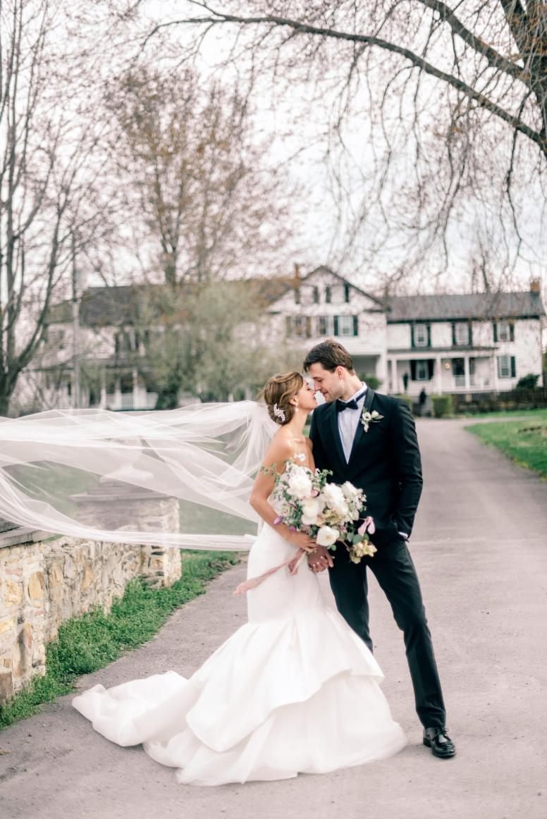 Bride and groom on their wedding day in front of a stone wall