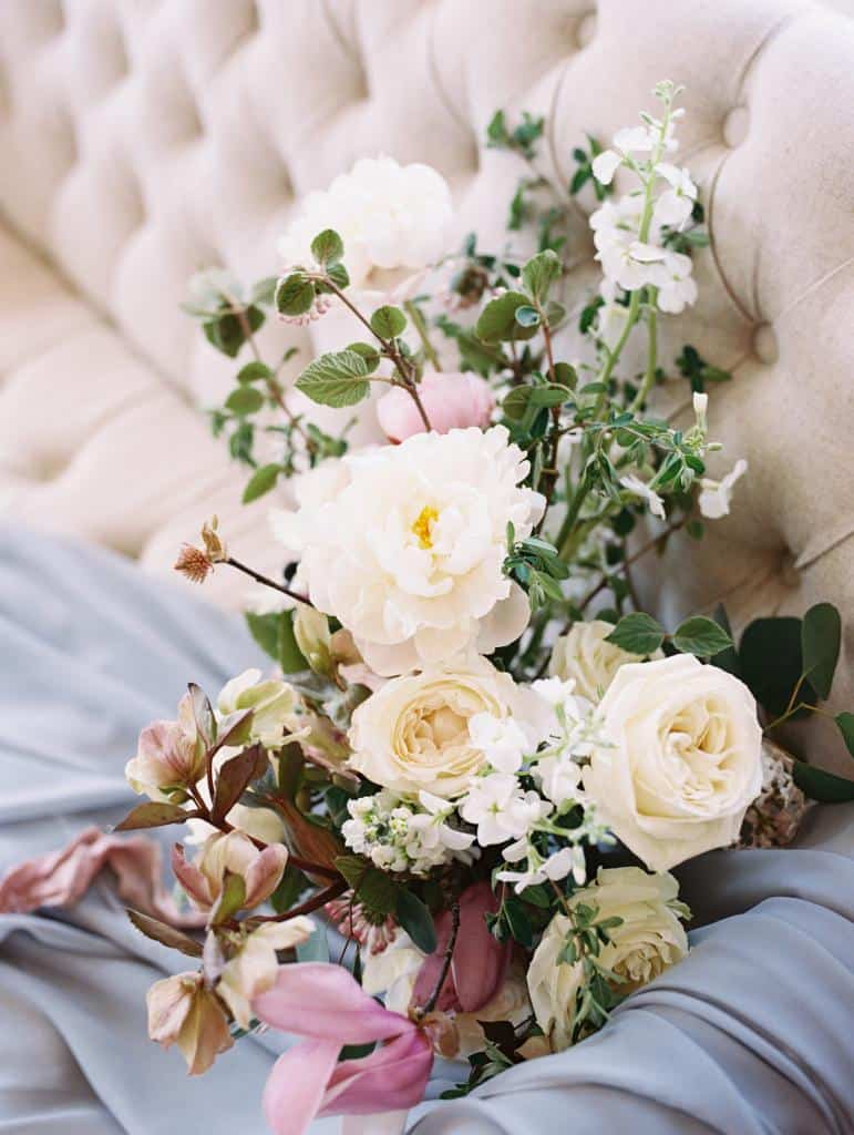 Bouquet of roses, peonies and anemonies on a cream colored settee.